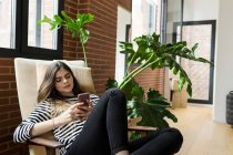Young woman sitting in armchair at home and using cell phone — Stock Photo