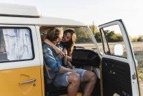 Glückliches Paar, das im Wohnmobil sitzt, sich umarmt und Getränke trinkt — Stockfoto