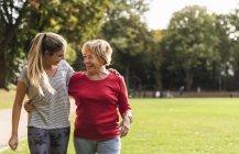 Petite-fille et grand-mère s'amusent, font du jogging ensemble dans le parc — Photo de stock