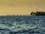 Maledives, Ross Atoll, plage avec parasols au coucher du soleil — Photo de stock