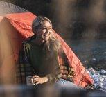 Mulher madura que acampa, sentando-se na frente da barraca — Fotografia de Stock