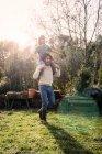 Pai brincando com seu filho, carregando-o em um jardim — Fotografia de Stock