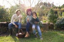 Happy family sitting in garden, taking a break, eating sandwiches — Stock Photo