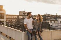 Felice giovane coppia rilassante sulla terrazza sul tetto al tramonto — Foto stock
