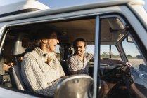 Glückliches Paar sitzt im Wohnmobil und lacht — Stockfoto