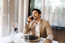 Man sitting at table in a restaurant talking on cell phone — Stock Photo