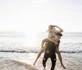 France, Brittany, happy young man carrying girlfriend piggyback at the beach — Stock Photo