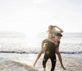 Frankreich, Bretagne, glücklicher junger Mann trägt Freundin Huckepack am Strand — Stockfoto
