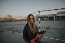 Портрет крутої молодої жінки з гітарою на спортивному полі. — стокове фото