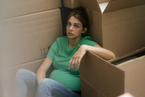 Exhausted pregnant woman sitting on floor surrounded by cardboard boxes — Stock Photo