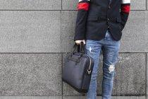 Primo piano di elegante uomo d'affari in piedi di fronte al muro grigio che tiene una borsa — Foto stock