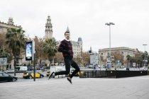 Hombre joven con ropa casual saltando - foto de stock