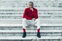 Портрет стильного молодого человека в красном свитере и носках, сидящих на лестнице — стоковое фото