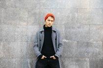 Портрет стильного молодого человека в кепке, черной водолазке и сером пальто — стоковое фото