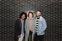 Ritratto di tre amici sorridenti in piedi a una parete nera — Foto stock