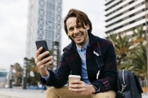 Spain, Barcelona, happy man sitting in the city with takeaway coffee and cell phone — Stock Photo