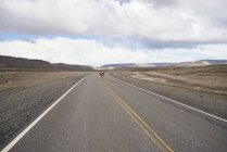 Argentina, Patagonia, National Route 40, Guanaco crossing empty road in the middle of desert — Stock Photo
