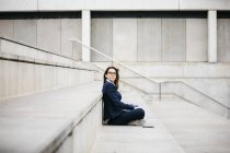 Businesswoman sitting outdoors on stairs with laptop — Stock Photo