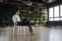 Homme d'affaires assis sur la chaise dans la pensée de bureau vert — Photo de stock