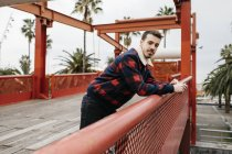 Young man with casual clothes on a red bridge looking at camera — Stock Photo