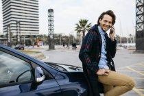Espanha, Barcelona, homem sorridente no celular do lado de fora do carro na cidade — Fotografia de Stock