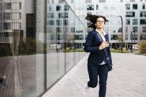 Empresária correndo fora do prédio de escritórios na cidade — Fotografia de Stock