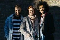 Portrait de trois amis heureux dans l'ombre à un mur de brique — Photo de stock