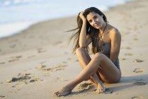 Ritratto di bella donna in costume da bagno seduta sulla spiaggia — Foto stock