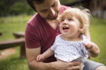 Отец одевает своего маленького сына в саду — стоковое фото