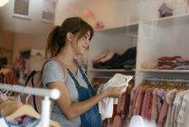Sorrindo mulher grávida comprando roupas de bebê em uma boutique — Fotografia de Stock