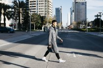 Spain, Barcelona, young man crossing the street — Stock Photo