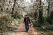 Старший мужчина ищет грибы в лесу — стоковое фото