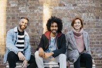 Ritratto di tre amici felici seduti su una panchina di fronte ad una parete di mattoni — Foto stock