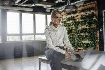 Щасливий ділової жінки в офісі за допомогою ноутбука — стокове фото