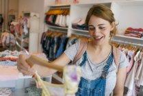 Glücklich schwangere Frau kauft Babykleidung in einer Boutique ein — Stockfoto