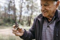 Sorrindo homem sênior segurando cogumelos encontrados — Fotografia de Stock
