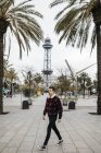 Spain, Barcelona, Young man with casual clothes walking on a square — Stock Photo