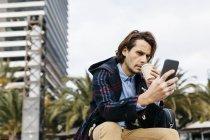Espanha, Barcelona, homem sério sentado na cidade com café takeaway e telefone celular — Fotografia de Stock