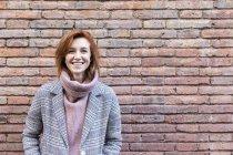 Portrait d'une jeune femme heureuse debout devant un mur de brique — Photo de stock