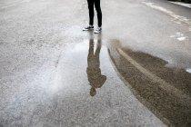 Riflessione di un uomo in una pozzanghera sul pavimento — Foto stock