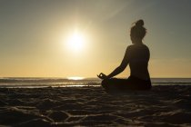 Женщина медитирует на пляже под вечерним солнцем — стоковое фото