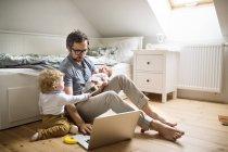 Père avec son petit fils et sa petite fille qui travaillent à la maison — Photo de stock