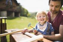 Vater und kleiner Sohn arbeiten mit Hammer im Garten — Stockfoto