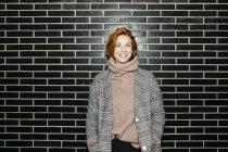 Portrait d'une jeune femme heureuse debout devant un mur noir — Photo de stock
