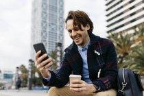 Espanha, Barcelona, homem feliz sentado na cidade com café takeaway e telefone celular — Fotografia de Stock