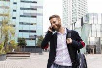 Elegante uomo d'affari che parla al cellulare in città — Foto stock