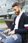 Elegante uomo d'affari seduto sulla panchina in città utilizzando il computer portatile — Foto stock