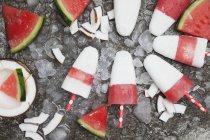 Lollies de coco de sandía caseras sobre hielo triturado - foto de stock