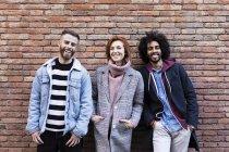 Portrait de trois amis heureux debout devant un mur de brique — Photo de stock