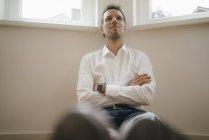 Бизнесмен с умными часами сидит на полу своей квартиры, мечтая — стоковое фото